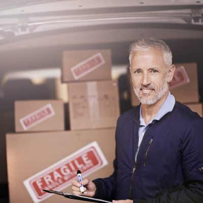 Portrait of a mature delivery man standing next to a van packed with boxes