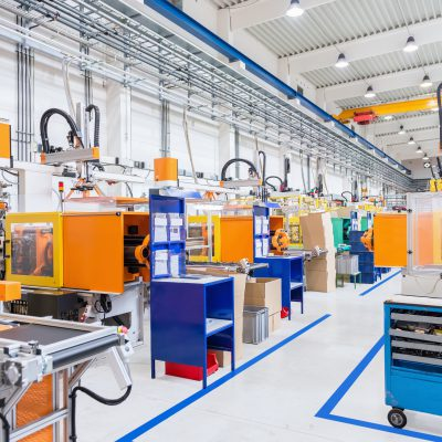 Horizontal image of huge new modern factory with robots and machines producing industrial plastic pieces and equipment. Futuristic machines having the monopole of all work, taking the place of human work.